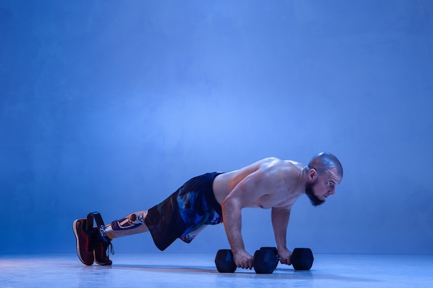 Sportowiec z niepełnosprawnością lub osoba po amputacji na białym tle na niebieskiej ścianie. profesjonalny sportowiec płci męskiej z treningiem protezy nogi z ciężarami w kolorze neonowym. sport niepełnosprawnych i pokonywanie, koncepcja odnowy biologicznej.