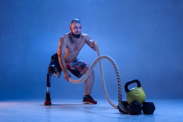 Sportowiec z niepełnosprawnością lub osoba po amputacji na białym tle na niebieskiej ścianie. profesjonalny sportowiec płci męskiej z treningiem protezy nogi z linami w kolorze neonowym. sport niepełnosprawnych i pokonywanie, koncepcja odnowy biologicznej.