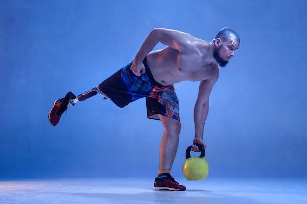 Sportowiec z niepełnosprawnością lub osoba po amputacji na białym tle na niebieskiej ścianie.