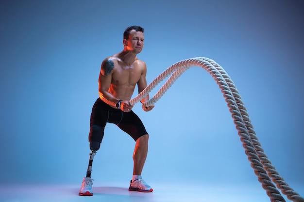 Sportowiec z niepełnosprawnością lub osoba po amputacji na białym tle na niebieskim tle studia