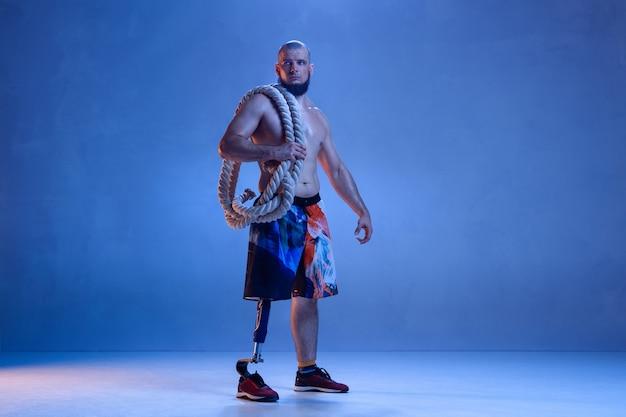 Sportowiec z niepełnosprawnością lub osoba po amputacji odizolowana na niebieskiej ścianie studia