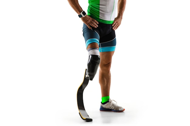 Sportowiec z niepełnosprawnościami lub po amputacji na białym tle na tle białego studia. profesjonalny biegacz z treningiem protezy nogi i ćwiczeniami w studio. niepełnosprawnych sport i pojęcie zdrowego stylu życia.