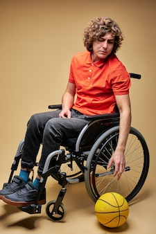 Sportowiec z powodu niepełnosprawności musiał zrezygnować ze sportu, siedzi na wózku inwalidzkim, patrząc na piłkę ze smutnym wyrazem twarzy.
