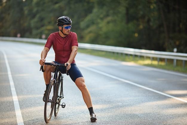 Sportowiec z silnymi nogami, ubrany w odzież sportową, relaksujący na czarnym rowerze wśród zieleni