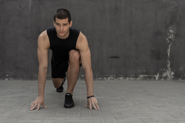 Sportowiec zaczyna swój sprint na szarym murze przemysłowym