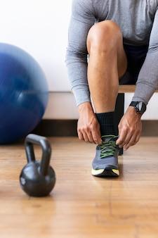 Sportowiec zawiązuje sznurowadła na siłowni
