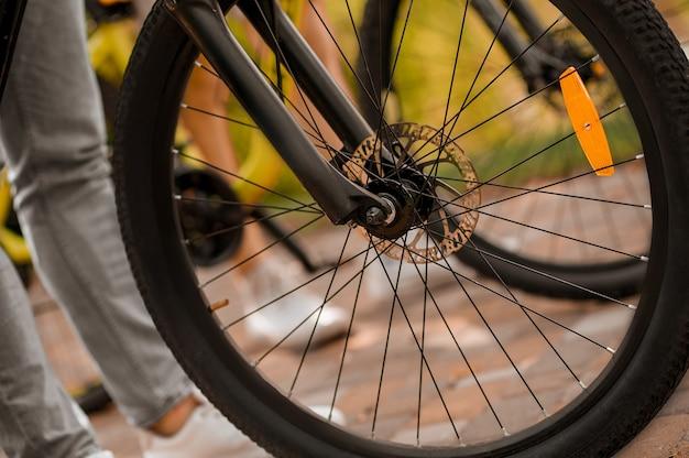 Sportowo aktywni ludzie rasy kaukaskiej z rowerami na zewnątrz