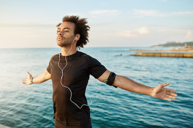 Sportowy afroamerykański mężczyzna rozciągający ramiona przed treningiem na świeżym powietrzu. szczupły i silny sportowiec w czarnym t-shircie, z otwartymi ramionami, oddychający świeżym morskim powietrzem.