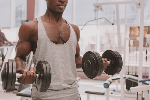 Sportowy afrykański mężczyzna pracujący z dumbbells przy gym out