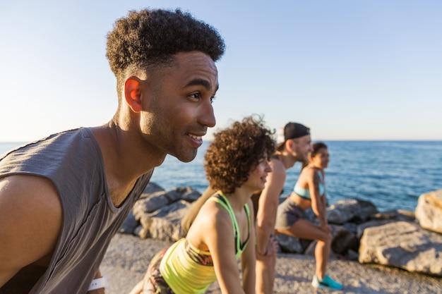 Sportowy afrykański mężczyzna przygotowuje się rozpocząć jogging z przyjaciółmi