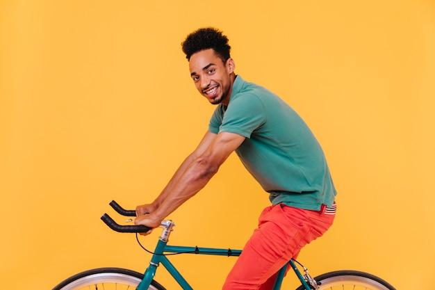 Sportowy afrykański mężczyzna z czarnymi włosami, pozowanie na rowerze. radosny uśmiechnięty facet wygłupiać się.