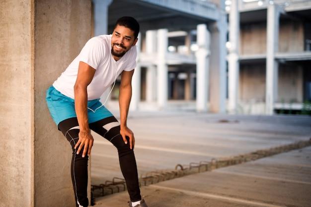 Sportowy atrakcyjny mężczyzna słuchanie muzyki i uśmiechanie się na treningu