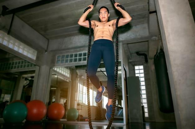 Sportowy azjatycki mężczyzna trenuje linowego wspinaczkowego ćwiczenie przy gym.