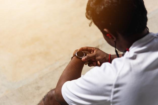 Sportowy biegacz czarny człowiek nosić nowoczesny czas inteligentny zegarek, który siedzi odpoczywa