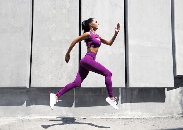 Sportowy biegacz w dynamicznym ruchu. dopasowana i zdrowa dziewczyna trenuje na ulicy. fitness kobieta.