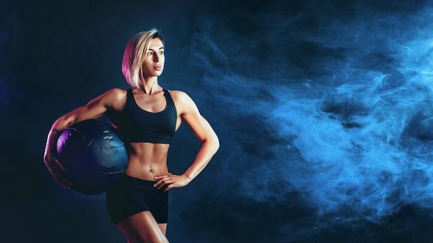 Sportowy blond kobieta w modnej odzieży sportowej z piłką lekarską. fotografia mięśniowa kobieta na zmrok ścianie z dymem. siła i motywacja.