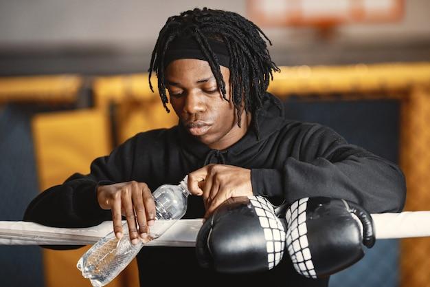 Sportowy boks mężczyzna. zdjęcie boksera na ringu. afroamerykanin z butelką wody.