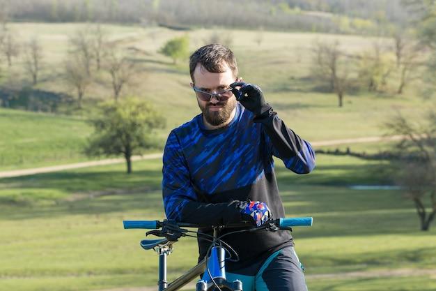 Sportowy brutalny brodaty facet na nowoczesnym rowerze górskim piękny widok z góry