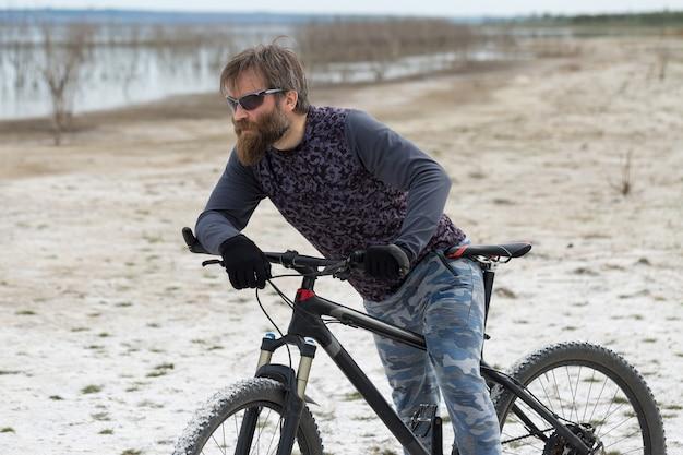 Sportowy brutalny brodaty facet na nowoczesnym rowerze górskim. rowerzysta w słonym, wyludnionym miejscu nad jeziorem.