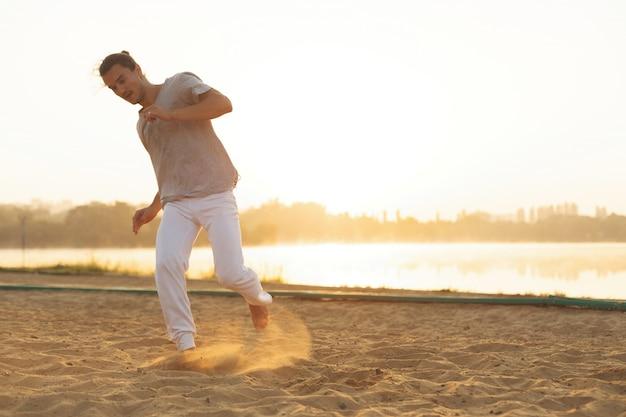 Sportowy capoeira wykonawca wykonuje ruchy na plaży