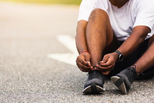 Sportowy czarny człowiek nosić zegarek siedzi siedzi on próbuje buty do biegania sznurowadło