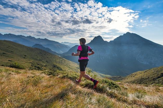 Sportowy człowiek górski jeździ po szlaku podczas treningu wytrzymałościowego