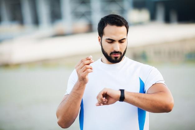 Sportowy człowiek za pomocą słuchawek do słuchania muzyki na poranny bieg w parku.