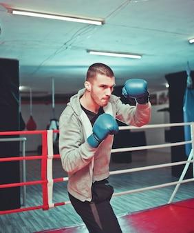 Sportowy facet bokser boks na ringu na siłowni. proces szkolenia boksera