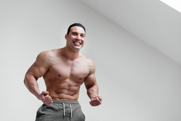 Sportowy facet krzyczy z wściekłości na białym tle. gniew. zagrożenie