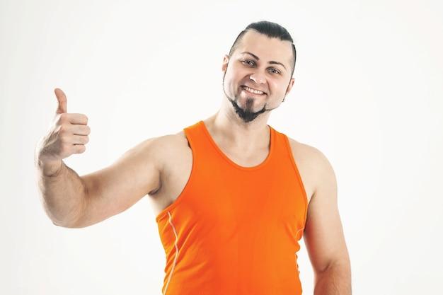 Sportowy facet - kulturysta w dżinsach i pomarańczowej koszuli robi kciukiem w górę gestem ręki. na zdjęciu jest puste miejsce na twój tekst