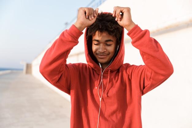 Sportowy facet na świeżym powietrzu na plaży, słuchając muzyki