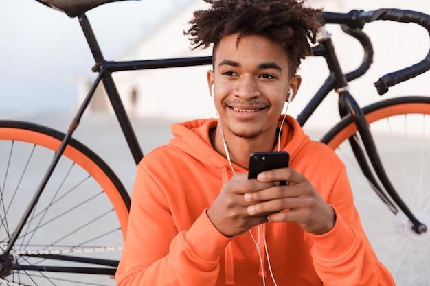 Sportowy facet na świeżym powietrzu na plaży z rowerem przy użyciu telefonu komórkowego słuchania muzyki
