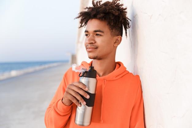 Sportowy facet na zewnątrz na plaży trzymając butelkę wody pitnej