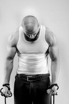 Sportowy facet pozowanie na białej ścianie. fotografia sportowa, piękna, czarno-biała.