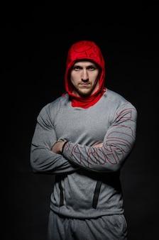 Sportowy facet stoi w studio na tle ciemnej przestrzeni w kapturze. sport, uroda.