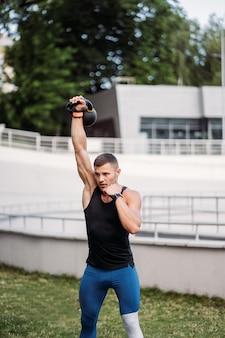 Sportowy facet trenujący z kettlebell.