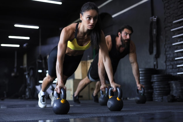 Sportowy indyjski mężczyzna i kobieta robi pompki w siłowni.
