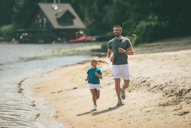 Sportowy jak ojciec. pełna długość wesołego ojca i córki w sportowych ubraniach biegających razem nad brzegiem rzeki