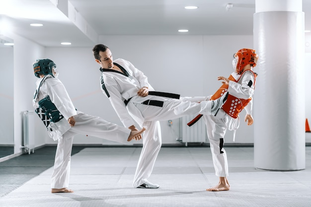 Sportowy kaukaski chłopców trenujących taekwondo w białej siłowni. trener demonstrujący kopnięcie.