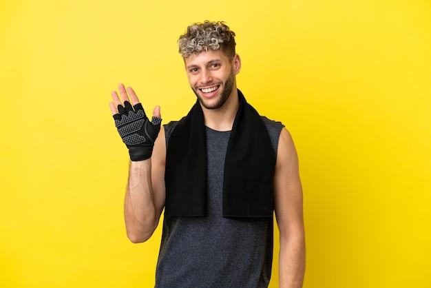 Sportowy kaukaski mężczyzna na żółtym tle pozdrawiający ręką ze szczęśliwym wyrazem twarzy
