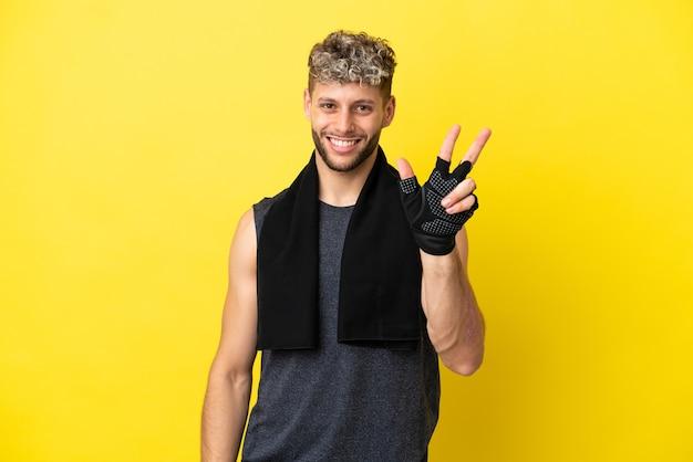 Sportowy kaukaski mężczyzna na żółtym tle szczęśliwy i liczący trzy palcami
