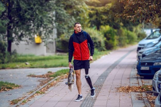 Sportowy kaukaski niepełnosprawny mężczyzna ze sztuczną nogą, w sportowej odzieży i plecaku, spacerujący po ulicy. w rękach jest sztuczna noga.