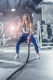 Sportowy kobieta ćwiczenia z lin bojowych na siłowni fitness.