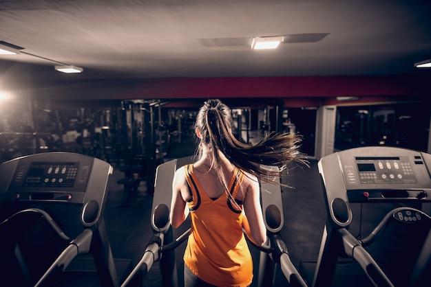Sportowy kobieta działa na bieżni. wnętrze siłowni.