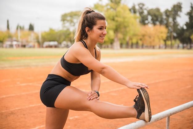 Sportowy kobieta rozciąganie na torze stadionu