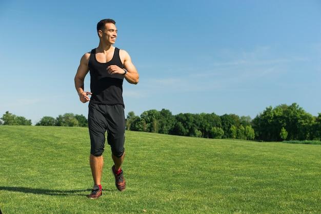 Sportowy mężczyzna biega plenerowy w parku