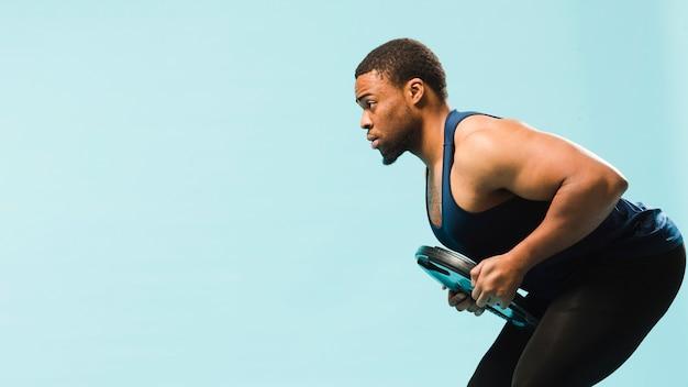 Sportowy mężczyzna ćwiczy z ciężarami