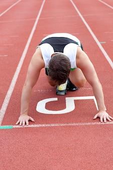 Sportowy mężczyzna czekanie w zaczyna bloku