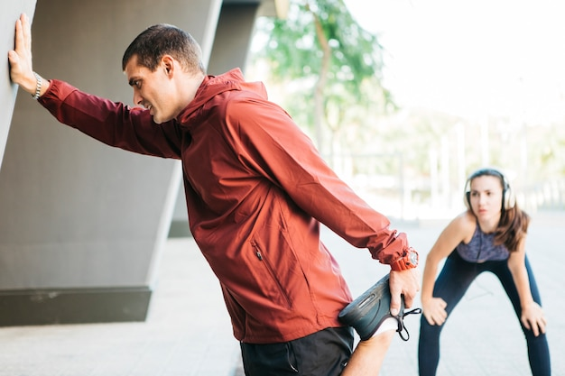 Sportowy mężczyzna i kobieta rozciąganie w środowisku miejskim