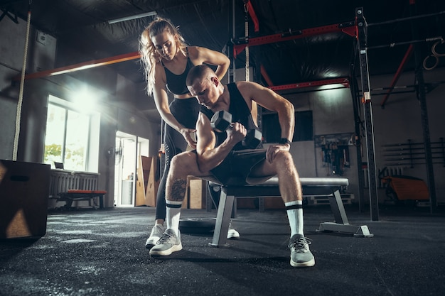 Sportowy mężczyzna i kobieta z hantlami